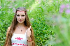 Ritratto di giovane bella ragazza dello slavo con capelli lunghi ed il vestito etnico dallo slavo in boschetti di erba alta Fotografia Stock Libera da Diritti