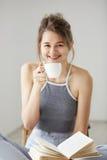 Ritratto di giovane bella ragazza felice che sorride esaminando la tazza di caffè ed il libro hoding della macchina fotografica c Fotografia Stock