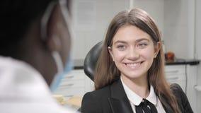 Ritratto di giovane bella ragazza nella sedia del dentista alla clinica dentaria Medicina, salute, concetto di stomatologia denti stock footage