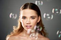 Ritratto di giovane bella ragazza in studio, con trucco professionale Fucilazione di bellezza La bellezza delle bolle di sapone E fotografia stock libera da diritti
