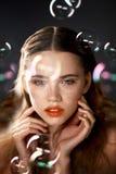 Ritratto di giovane bella ragazza in studio, con trucco professionale Fucilazione di bellezza La bellezza delle bolle di sapone E immagine stock
