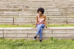 Ritratto di giovane bella seduta afroamericana felice della donna Fotografie Stock