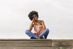 Ritratto di giovane bella seduta afroamericana felice della donna Immagini Stock Libere da Diritti