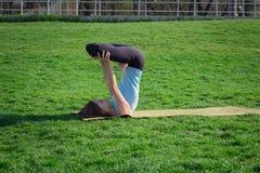 Ritratto di giovane bella signora che medita nella posa di yoga su erba verde Immagini Stock