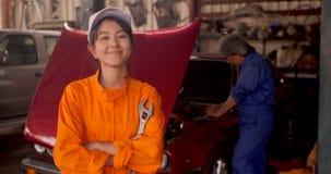 Ritratto di giovane bello meccanico di automobile in un'officina dell'automobile video d archivio