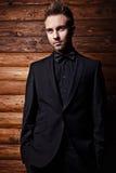 Ritratto di giovane bello uomo alla moda contro la parete di legno. Fotografia Stock