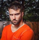 Ritratto di giovane bello uomo in arancia, contro fondo all'aperto Fotografie Stock