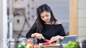 Ritratto di giovane casalinga femminile asiatica adorabile durante la cottura del pasto sano fresco alla cucina stock footage