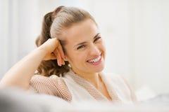 Ritratto di giovane casalinga sorridente che si siede sul divano Fotografia Stock