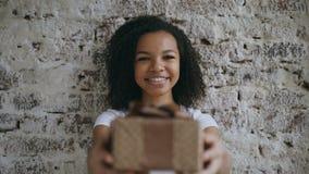 Ritratto di giovane contenitore e di sorridere di regalo africano felice del presente della ragazza nella macchina fotografica Fotografia Stock Libera da Diritti