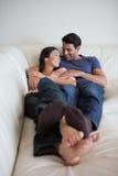 Ritratto di giovane coppia che si trova su un sofà Immagini Stock Libere da Diritti