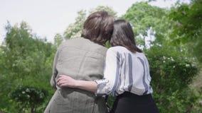 Ritratto di giovane coppia felice in abbigliamento casual che spende insieme tempo nel parco, avendo una data Amanti che si siedo video d archivio