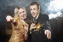 Ritratto di giovane coppia felice con i vetri e le stelle filante fotografia stock libera da diritti