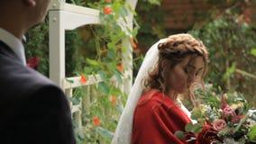 Ritratto di giovane coppia nell'amore in un giardino vicino ad un gazebo video d archivio
