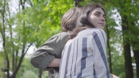 Ritratto di giovane coppia sveglia in abbigliamento casual che spende insieme tempo nel parco, avendo una data Amanti che si sied video d archivio