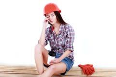 Ritratto di giovane costruttore femminile nella seduta del casco, sul bianco Fotografia Stock