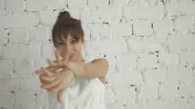 Ritratto di giovane dancing felice della donna di forma fisica sul fondo bianco del muro di mattoni video d archivio