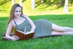 Ritratto di giovane dello studente libro di lettura castana splendido all'aperto Immagini Stock Libere da Diritti