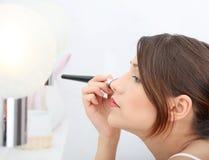 Ritratto di giovane donna adulta che applica blusher Immagine Stock Libera da Diritti