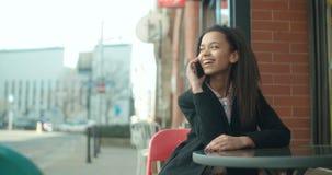 Ritratto di giovane donna afroamericana che per mezzo del telefono video d archivio