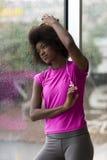 Ritratto di giovane donna afroamericana in palestra mentre mus d'ascolto Fotografia Stock