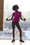 Ritratto di giovane donna afroamericana in palestra mentre mus d'ascolto Immagine Stock