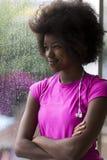 Ritratto di giovane donna afroamericana in palestra mentre mus d'ascolto Fotografie Stock