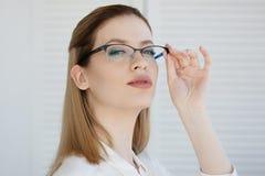 Ritratto di giovane donna alla moda di affari in camicia bianca e vetri immagine stock libera da diritti