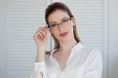 Ritratto di giovane donna alla moda di affari in camicia bianca e vetri fotografie stock libere da diritti