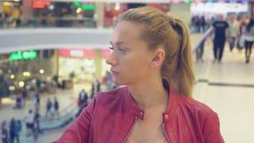 Ritratto di giovane donna annoiata in un supermercato in mezzo del passare i clienti 4K offuscamento video d archivio