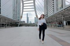 Ritratto di giovane donna asiatica attraente di affari che cammina e che esamina lontano il marciapiede del fondo urbano della ci Fotografie Stock Libere da Diritti