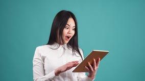 Ritratto di giovane donna asiatica felice che per mezzo della compressa digitale video d archivio