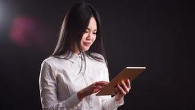 Ritratto di giovane donna asiatica felice che per mezzo della compressa digitale - isolata video d archivio