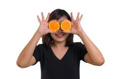 Ritratto di giovane donna asiatica tenendo le fette arancio davanti ai suoi occhi e sorriso isolate su fondo bianco Fotografia Stock