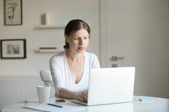 Ritratto di giovane donna attraente allo scrittorio con un computer portatile Immagini Stock Libere da Diritti