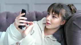 Ritratto di giovane donna attraente che chiacchiera entusiasta facendo uso dello smartphone che si trova sullo strato stock footage