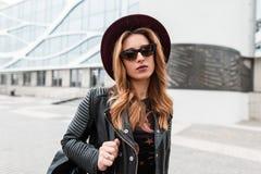 Ritratto di giovane donna attraente dai capelli rossi dei pantaloni a vita bassa in un cappello elegante in occhiali da sole d'av immagini stock libere da diritti