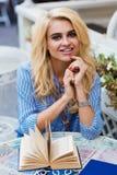 Ritratto di giovane donna bionda affascinante con il bello sorriso che posa mentre sedendosi con il libro in caffè del marciapied Fotografie Stock Libere da Diritti