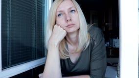 Ritratto di giovane donna bionda attraente graziosa con gli occhi azzurri che stanno vicino alla finestra aperta di mattina, beve archivi video
