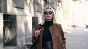 Ritratto di giovane donna bionda attraente nella città di autunno La ragazza ha lo sguardo alla moda, gli occhiali da sole e pier stock footage