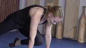 Ritratto di giovane donna bionda che sta facendo la posa del planck sulla sua classe di yoga archivi video
