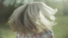 Ritratto di giovane donna bionda che sta nel parco sul tramonto e che esamina macchina fotografica Ragazza felice che spende temp stock footage