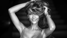 Ritratto di giovane donna bionda meravigliosa con capelli lunghi che esaminano macchina fotografica, sorridente Immagine Stock