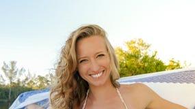 Ritratto di giovane donna bionda normale soddisfatta e che sorride degli occhi azzurri in natura con una sciarpa bianca e blu del fotografie stock
