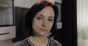 Ritratto di giovane donna castana caucasica graziosa che sorride a casa archivi video