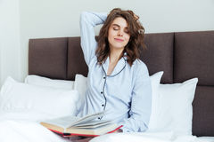 Ritratto di giovane donna castana in libro di lettura dei pigiami Immagine Stock