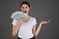 Ritratto di giovane donna castana in maglietta del whote che tiene le banconote dei soldi e che celebra immagine stock libera da diritti