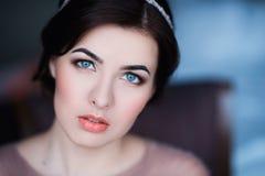 Ritratto di giovane donna castana in un bello vestito con trucco e l'acconciatura Fotografia Stock