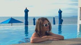 Ritratto di giovane donna caucasica che sorride nella piscina Concetto perfetto di vacanza archivi video