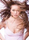 Ritratto di giovane donna con capelli lunghi saltati dai wi Fotografie Stock Libere da Diritti